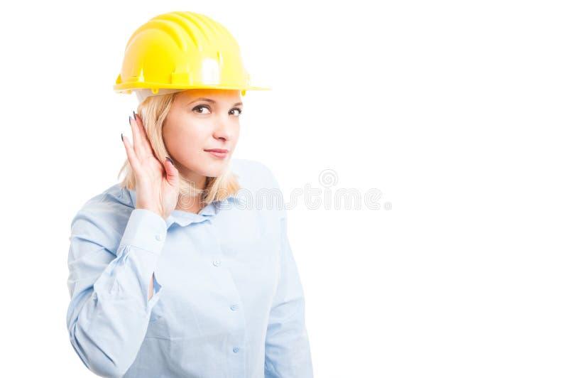 Casco d'uso dell'ingegnere di signora che fa gesto di udito immagine stock libera da diritti