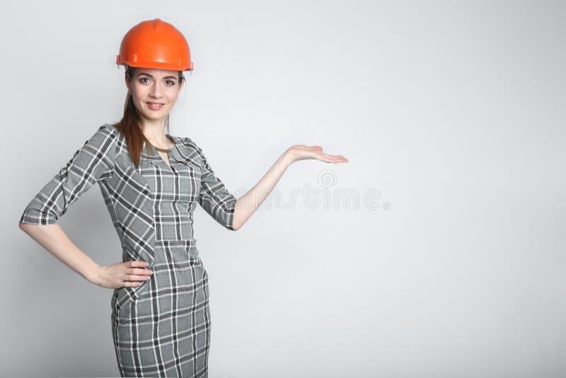 Casco d'uso sorridente del costruttore della donna di affari che indica dito sullo spazio della copia fotografie stock