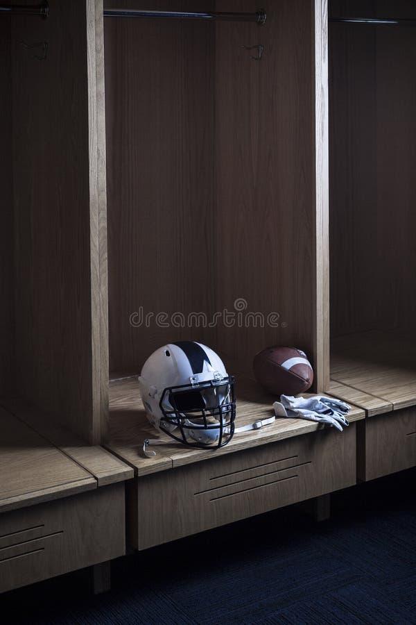 Casco de fútbol americano que se sienta en un vestuario del fútbol americano y imagenes de archivo