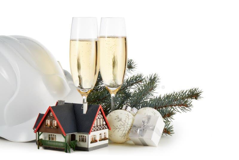 Casco de la construcción, ramas de árbol de abeto, casa modelo, dos vidrios con el champange y el ornamento de la Navidad aislado foto de archivo
