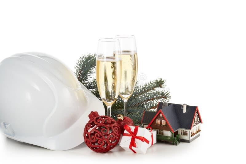Casco de la construcción, ramas de árbol de abeto, casa modelo, dos vidrios con el champange y el ornamento de la Navidad aislado foto de archivo libre de regalías