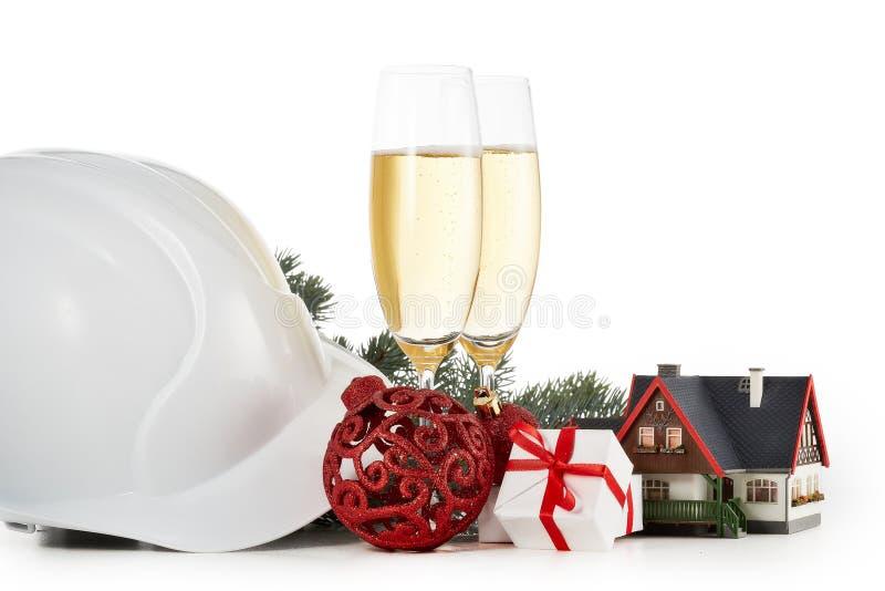 Casco de la construcción, ramas de árbol de abeto, casa modelo, dos vidrios con el champange y el ornamento de la Navidad aislado fotos de archivo