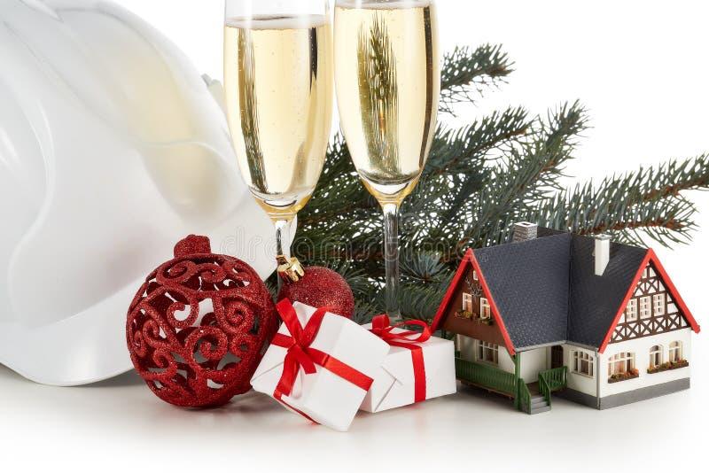 Casco de la construcción, ramas de árbol de abeto, casa modelo, dos vidrios con el champange y el ornamento de la Navidad aislado imagenes de archivo