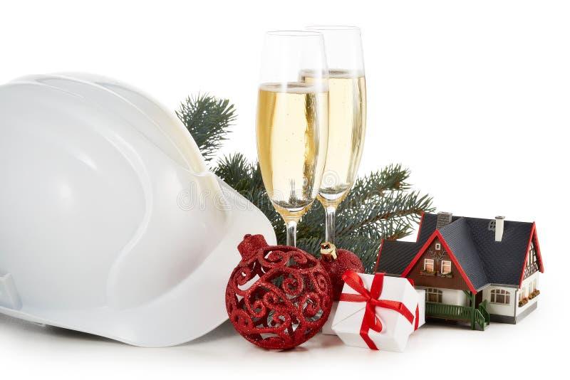 Casco de la construcción, ramas de árbol de abeto, casa modelo, dos vidrios con el champange y el ornamento de la Navidad aislado fotos de archivo libres de regalías