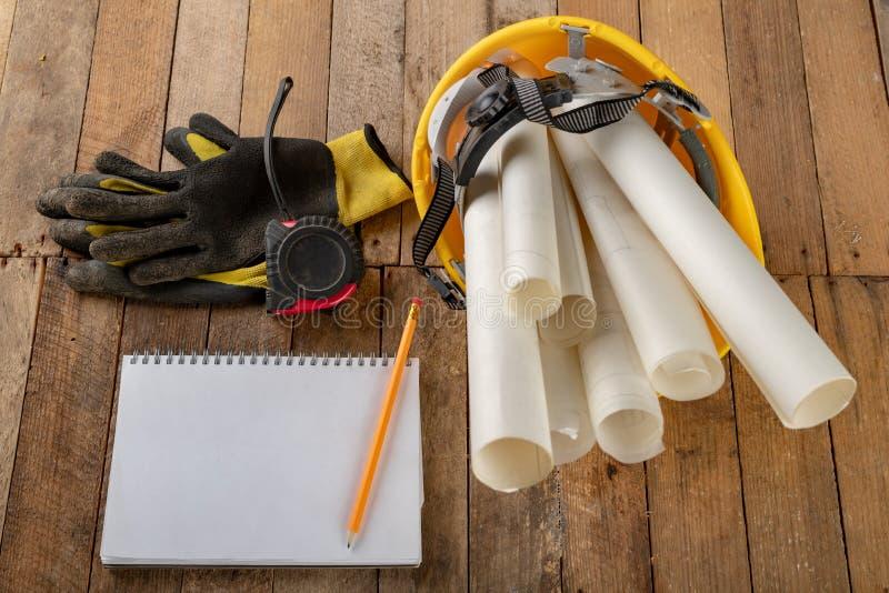 Casco de la construcción y rollo del pergamino con diseño Accesorios del ingeniero de construcción en una tabla de madera fotos de archivo