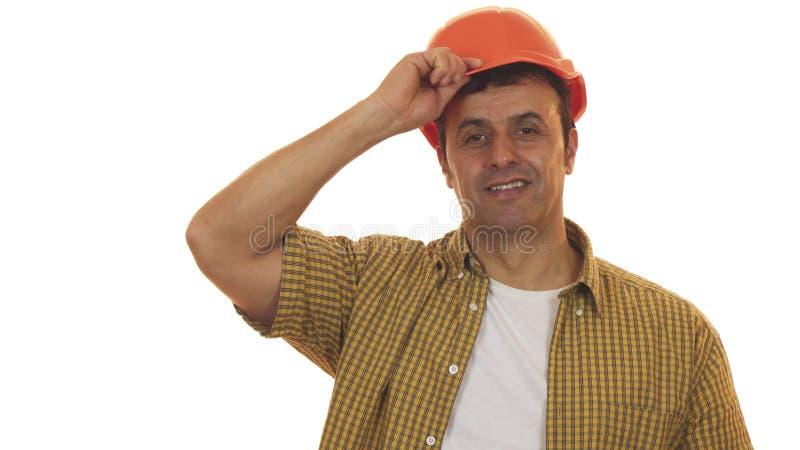 Casco de protección que lleva del ingeniero maduro hermoso que sonríe con confianza imagen de archivo libre de regalías