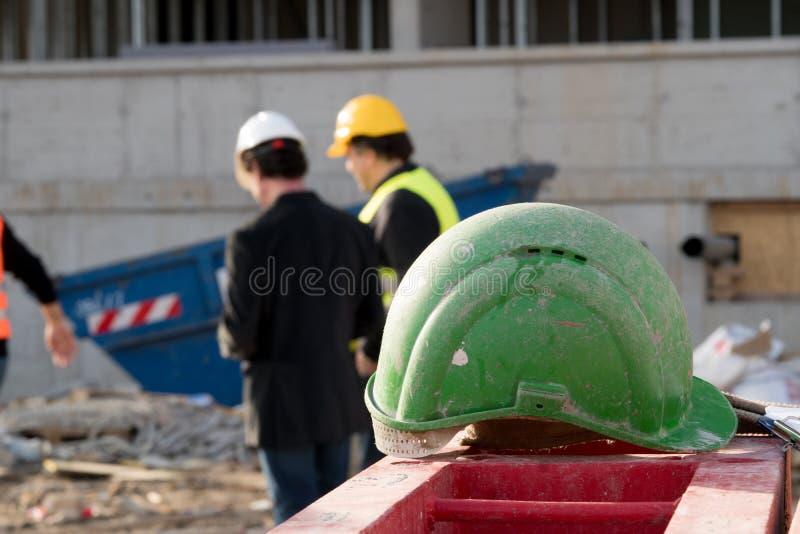 Casco de protección verde de la seguridad en primero plano Dos trabajadores de construcción encendido fuera del fondo enfocado fotos de archivo
