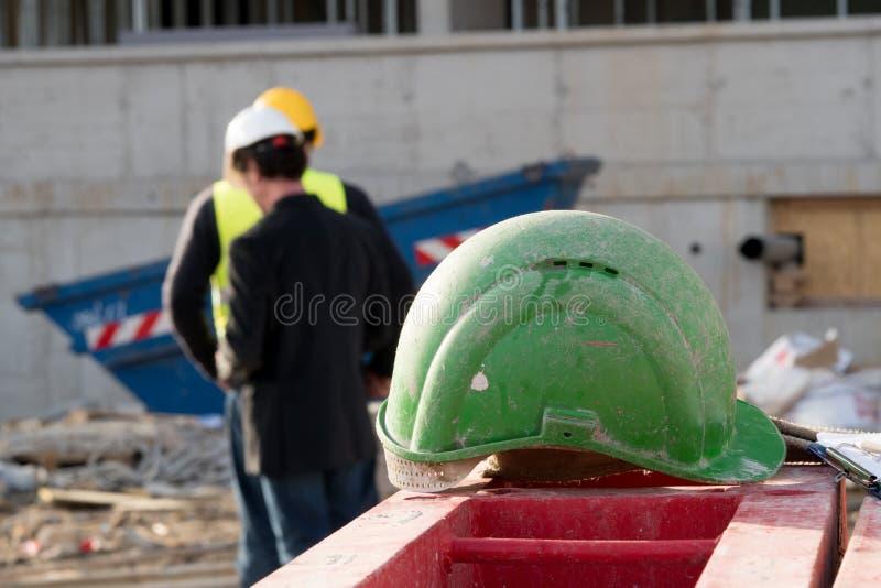 Casco de protección verde de la seguridad en primero plano Trabajadores de construcción en fondo imagenes de archivo
