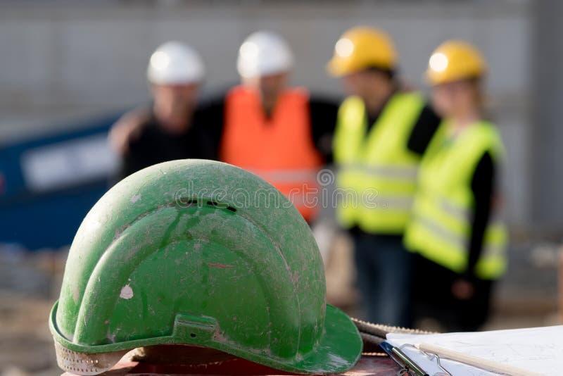 Casco de protección verde de la seguridad encendido fuera del fondo enfocado fotografía de archivo libre de regalías