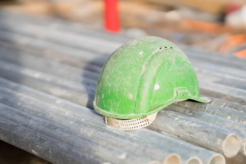 Casco de seguridad verde en los tubos del metal imágenes de archivo libres de regalías