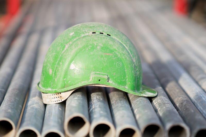 Casco de seguridad verde en los tubos del metal imagen de archivo