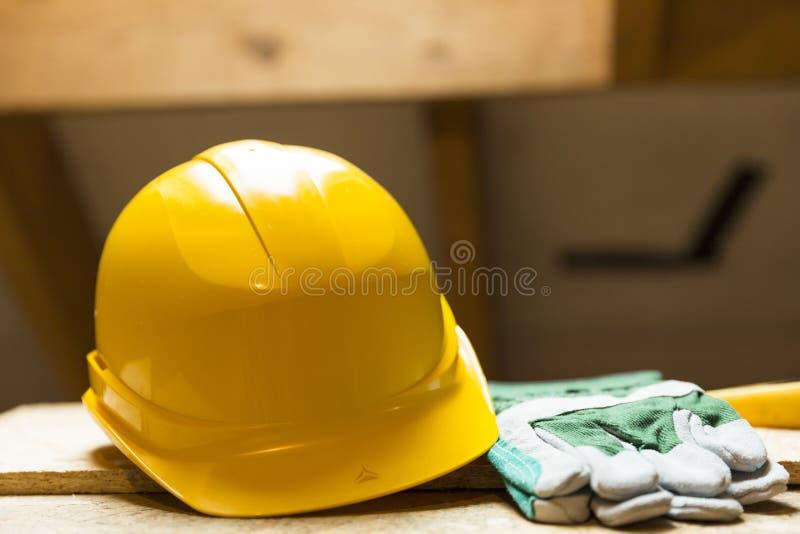 Casco de seguridad y guantes amarillos en superficie de funcionamiento en el sitio de la renovación del ático fotografía de archivo libre de regalías