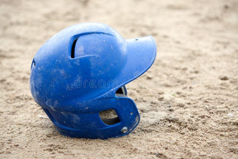 Casco del béisbol en arena imagenes de archivo