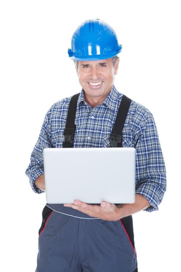 Casco del lavoratore e computer portatile d'uso usando fotografia stock libera da diritti