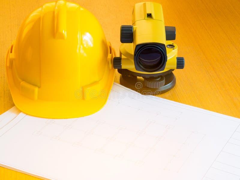 Casco del teodolito y de la construcción, rollos y planes En el escritorio fotos de archivo