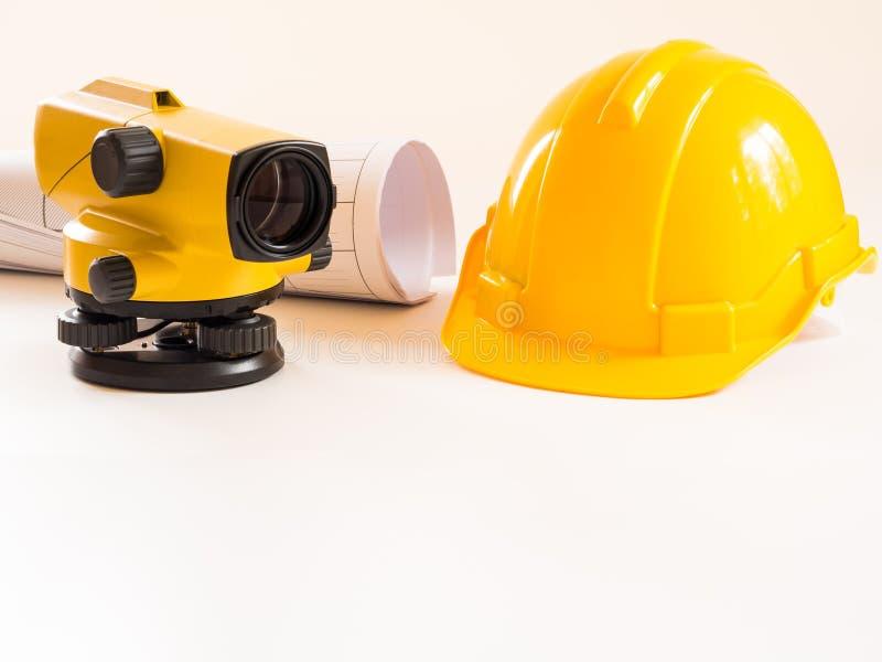Casco della costruzione e del teodolite, rotoli e piani Su fondo bianco Concetto di industria dell'edilizia immagini stock