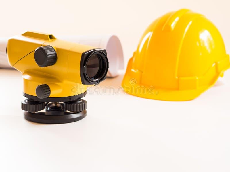 Casco della costruzione e del teodolite, rotoli e piani Su fondo bianco Concetto di industria dell'edilizia immagini stock libere da diritti