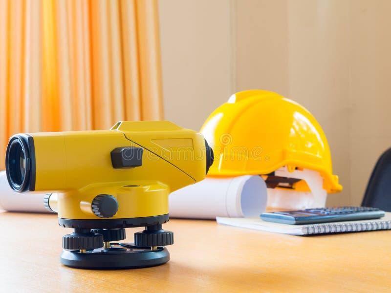 Casco della costruzione e del teodolite, rotoli e piani Sullo scrittorio Concetto di industria dell'edilizia fotografia stock libera da diritti