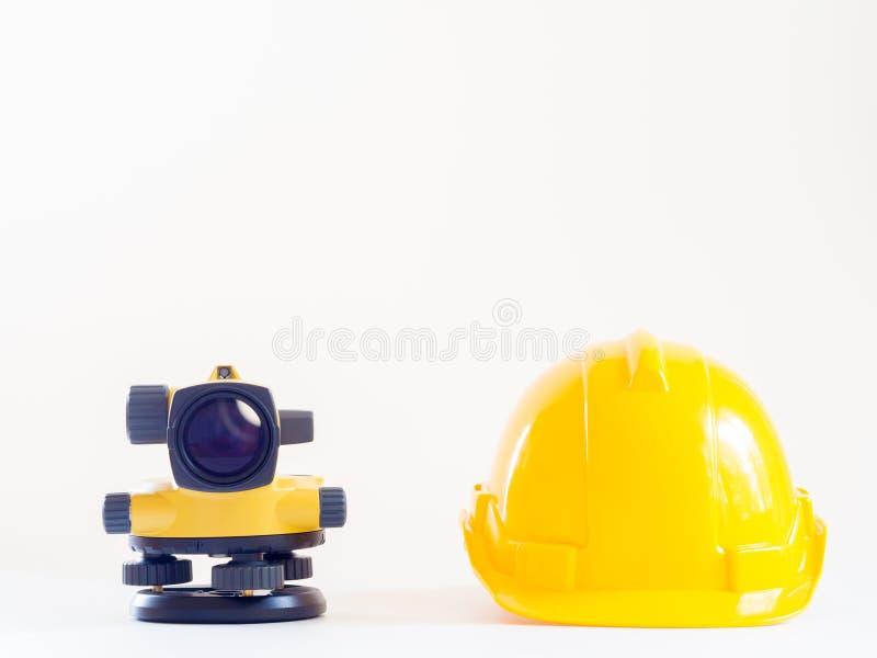 Casco della costruzione e del teodolite su fondo bianco fotografia stock libera da diritti