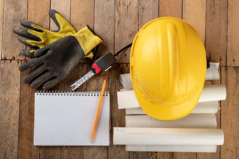 Casco della costruzione e rotolo di pergamena con progettazione Accessori dell'ingegnere di costruzione su una tavola di legno fotografie stock