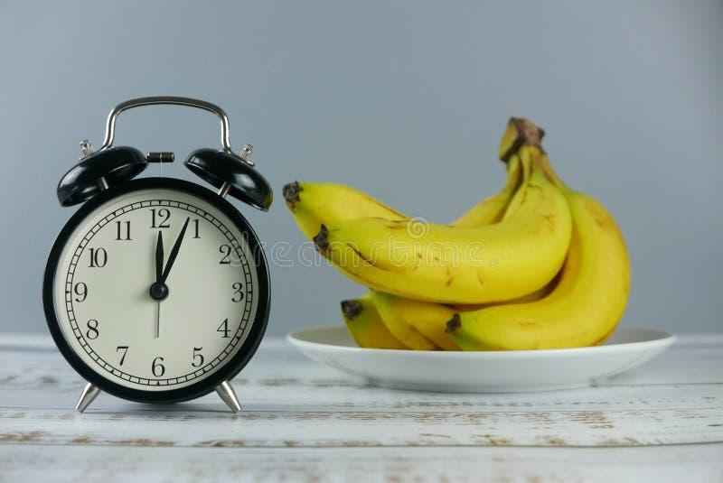 Casco di banane del fuoco selettivo e manifestazione 4 dell'orologio di tavola dell'allarme dopo 12 o' orologio su fondo di  immagini stock libere da diritti