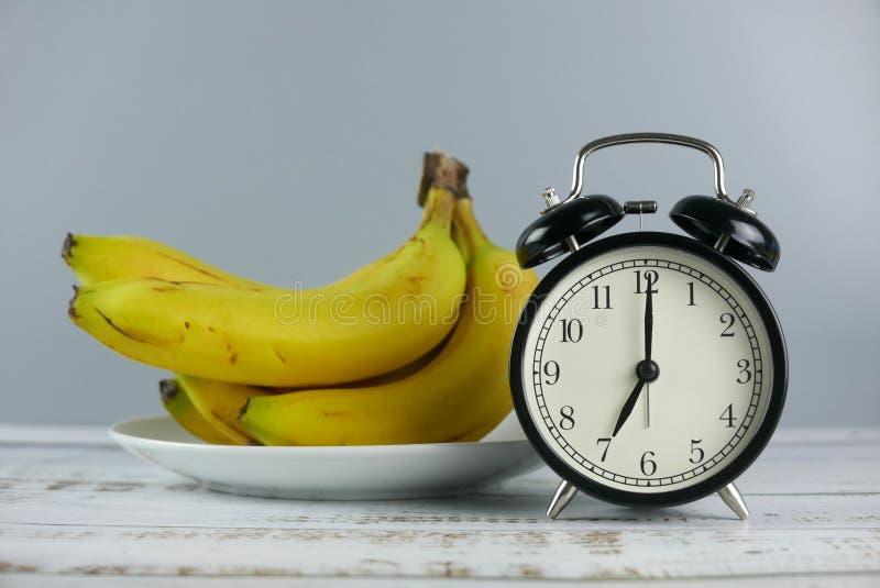 Casco di banane del fuoco selettivo e manifestazione 7 o' dell'orologio di tavola dell'allarme; orologio su fondo di legno fotografia stock