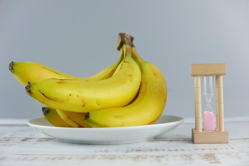 Casco di banane del fuoco selettivo ed orologio della sabbia su fondo di legno immagine stock libera da diritti