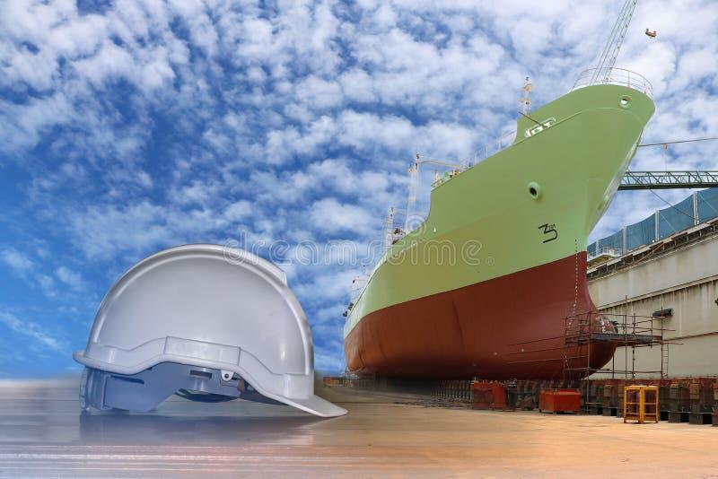 Casco di sicurezza bianco bianco del casco con la parte anteriore della riparazione navale in bacino galleggiante fotografie stock