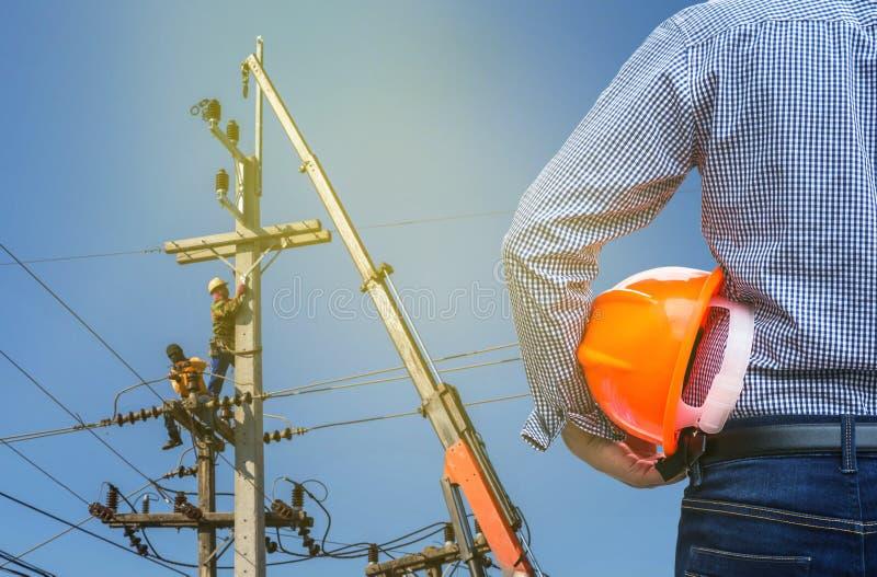 Casco di sicurezza della tenuta dell'elettrotecnico con gli elettricisti che lavorano al palo di energia elettrica con la gru fotografie stock libere da diritti