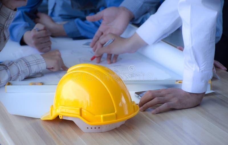 Casco di sicurezza disposto su un gruppo di ingegneria del tavolo di riunione , Costruendo concetto immagini stock libere da diritti