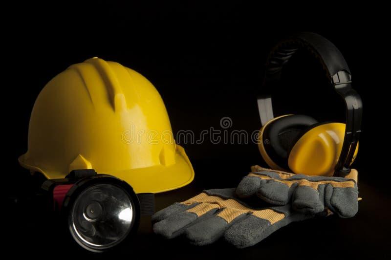 Casco di sicurezza giallo, guanto di cuoio, cuffia, lampada capa su fondo nero fotografie stock