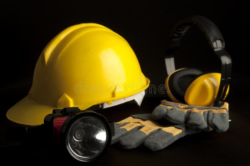 Casco di sicurezza giallo, guanto di cuoio, lampada capa, cuffia su fondo nero fotografie stock