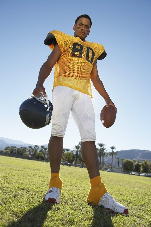 Casco e sfera della holding del giocatore di football americano fotografia stock libera da diritti