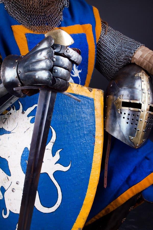 Casco, espada en manos imagen de archivo libre de regalías