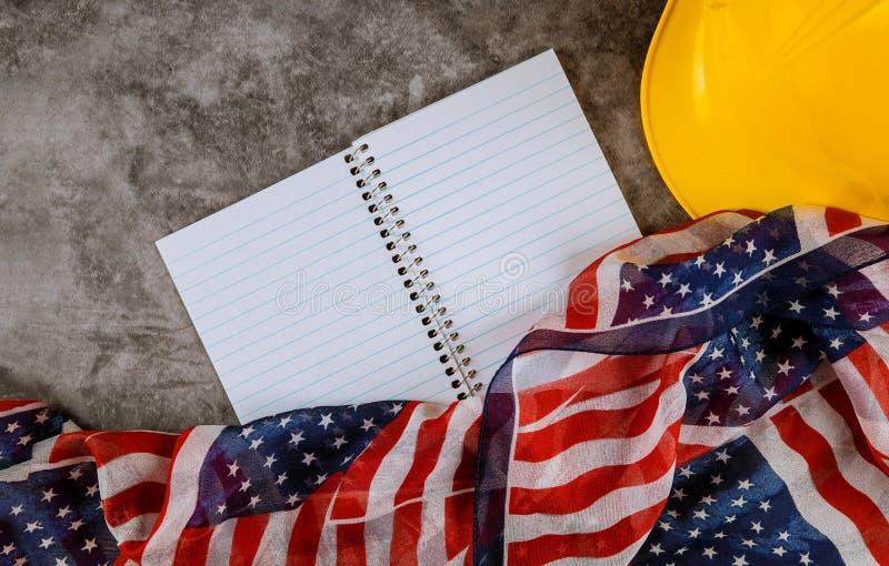 Casco giallo di concetto di festa del lavoro sulla bandiera nazionale di U.S.A. immagini stock