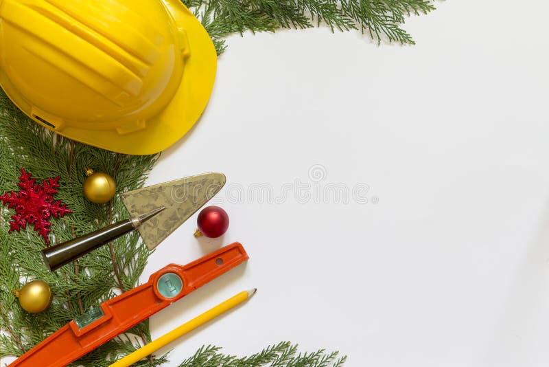 Casco, herramientas del albañil y decoraciones protectores de la Navidad en el fondo blanco foto de archivo