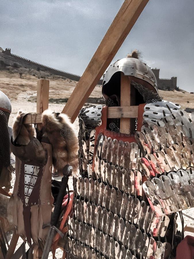 Casco metálico, armadura de placa brillante, espada contra la perspectiva de la pared antigua de la fortaleza, armadura romana an foto de archivo libre de regalías