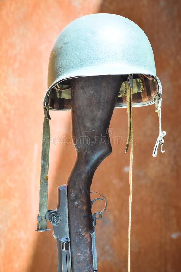 Casco militar apoyado en un arma de fuego Concepto de soldado desconocido fotografía de archivo