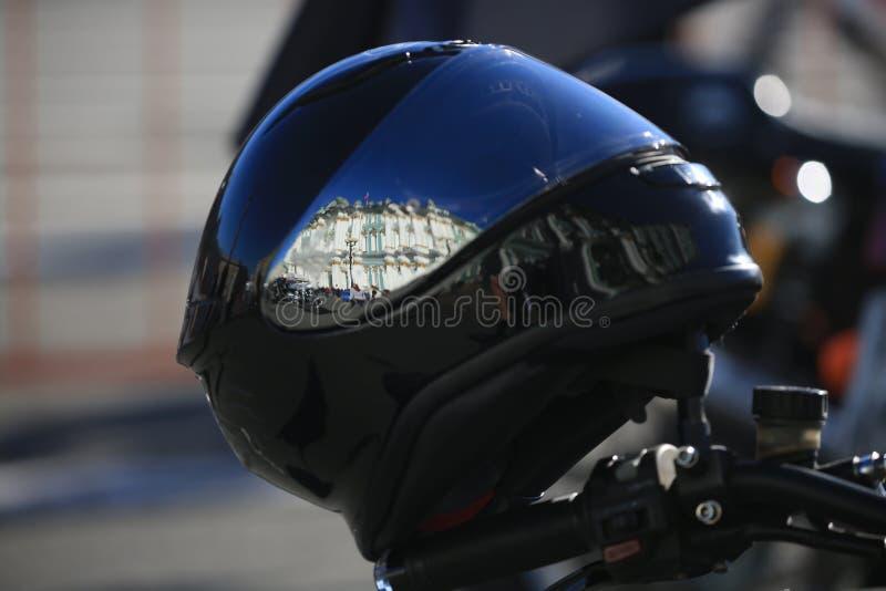Casco nero del motociclo e la riflessione della costruzione dell'eremo in  Fine in su immagini stock libere da diritti