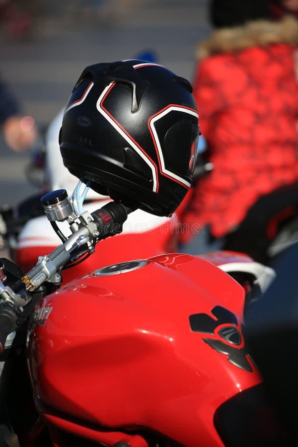 Casco nero sul manubrio della bici rossa sul primo piano di giorno soleggiato fotografie stock libere da diritti