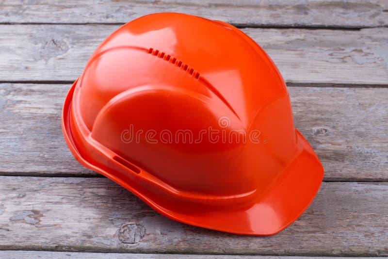 Casco protector industrial anaranjado en fondo de madera foto de archivo