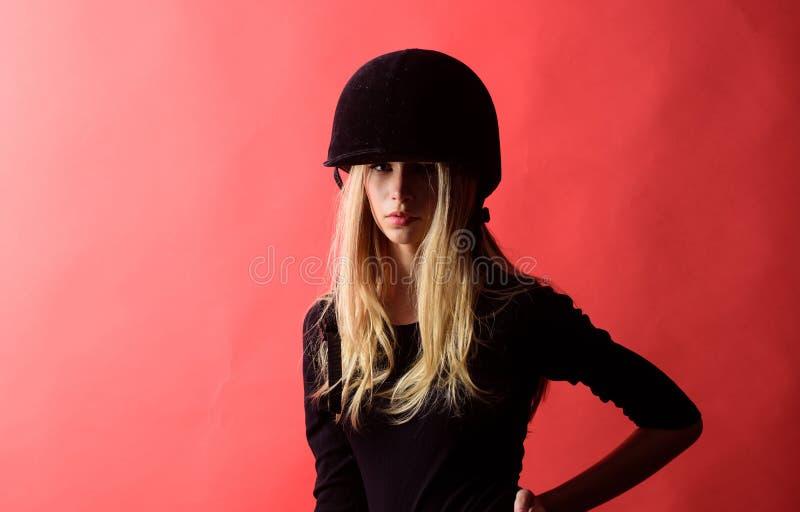 Casco protettivo di usura della puleggia tenditrice della ragazza su fondo rosso Concetto dell'attrezzatura di sport Regole di si fotografie stock