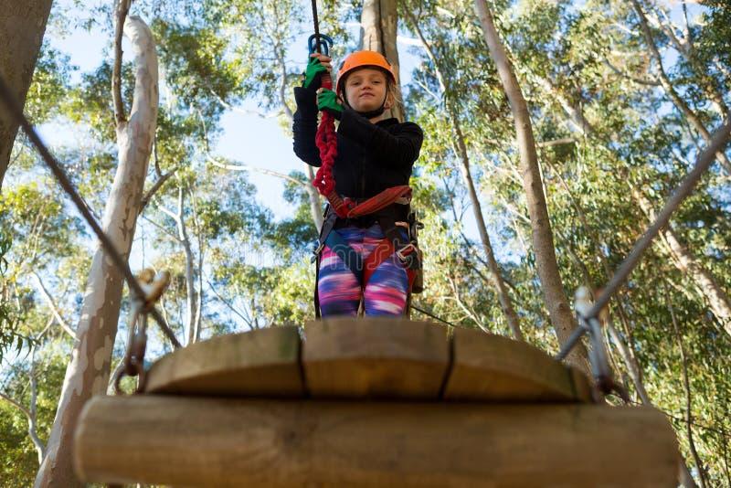 Casco que lleva de la niña que lleva a cabo la cuerda y la situación en la plataforma de madera fotografía de archivo
