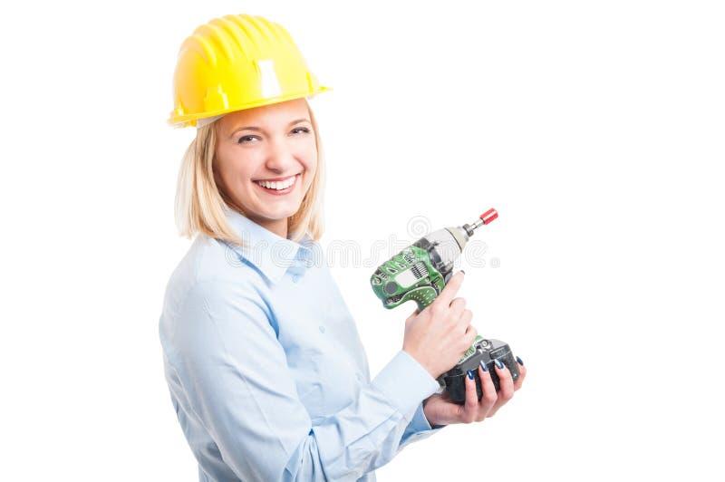 Casco que lleva del ingeniero de la mujer que sonríe celebrando el taladro fotografía de archivo libre de regalías