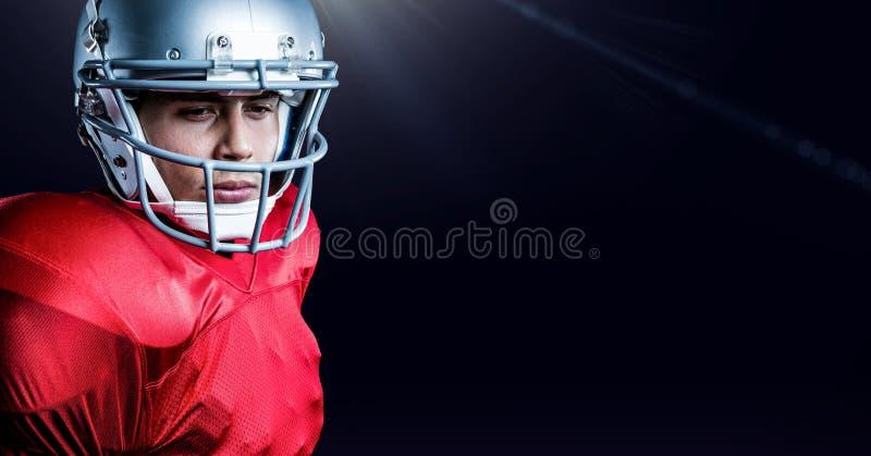 Casco que lleva del jugador de fútbol americano que se opone a fondo negro fotografía de archivo
