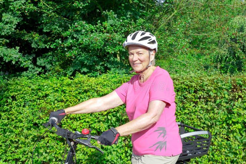 Casco senior della bicicletta della donna all'aperto immagini stock