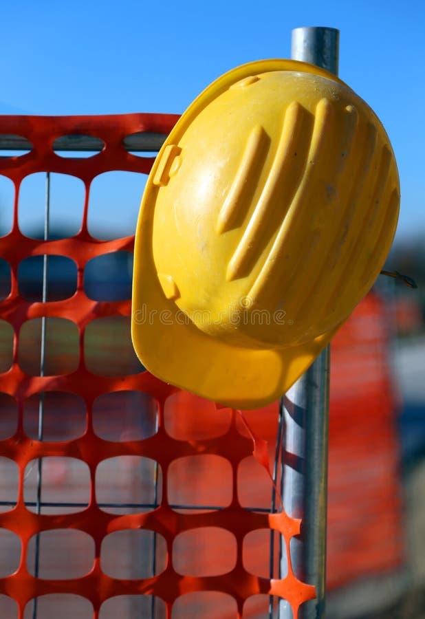 Casco sul sito della costruzione di strade e su una rete di sicurezza immagini stock libere da diritti