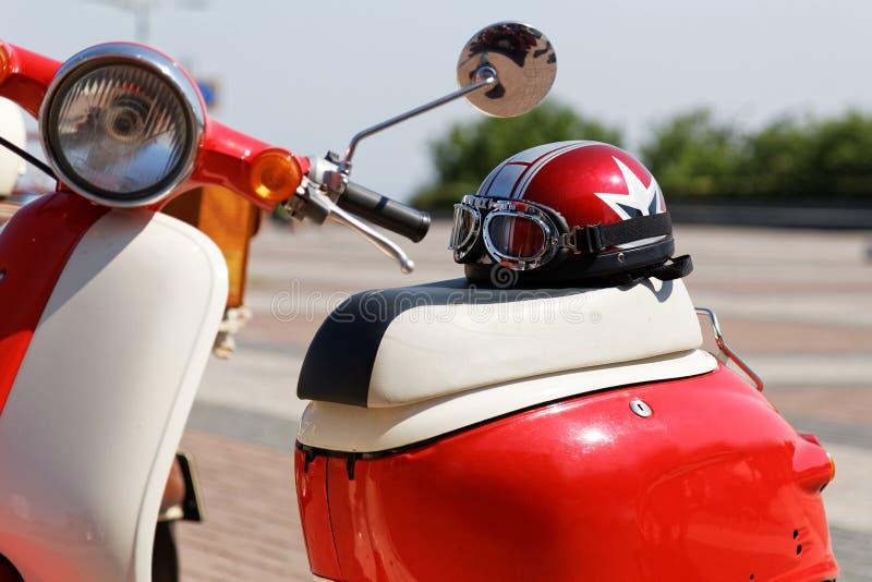 Casco y vidrios de Moto en el asiento de la vespa de motor fotos de archivo libres de regalías