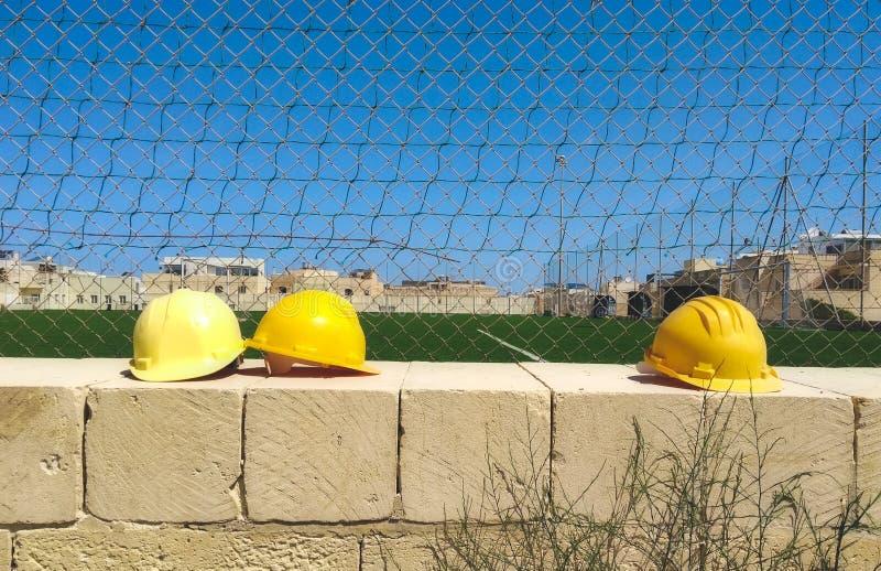 Cascos amarillos en una pared en un emplazamiento de la obra fotografía de archivo