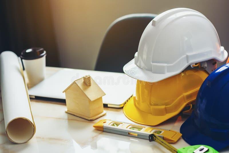 Cascos de seguridad blancos, amarillos y azules para proyectos de seguridad de los trabajadores en posición de ingenieros y en to foto de archivo